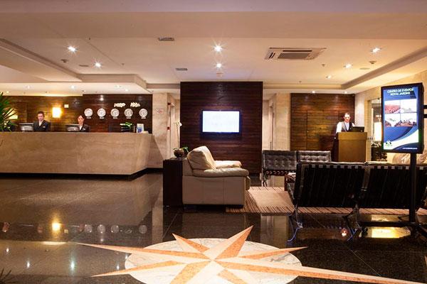 recepção de hotel com atendentes e sofás para descanso