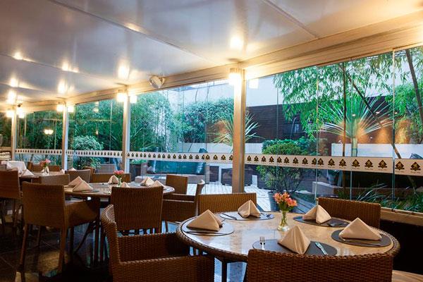 mesas enfileiradas com vista para jardim no hotel royal boutique