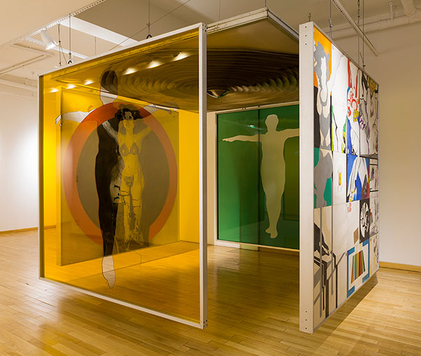 instalação de cinco placas multicoloridas com formas do corpo humano cercam o visitante em forma de caixa