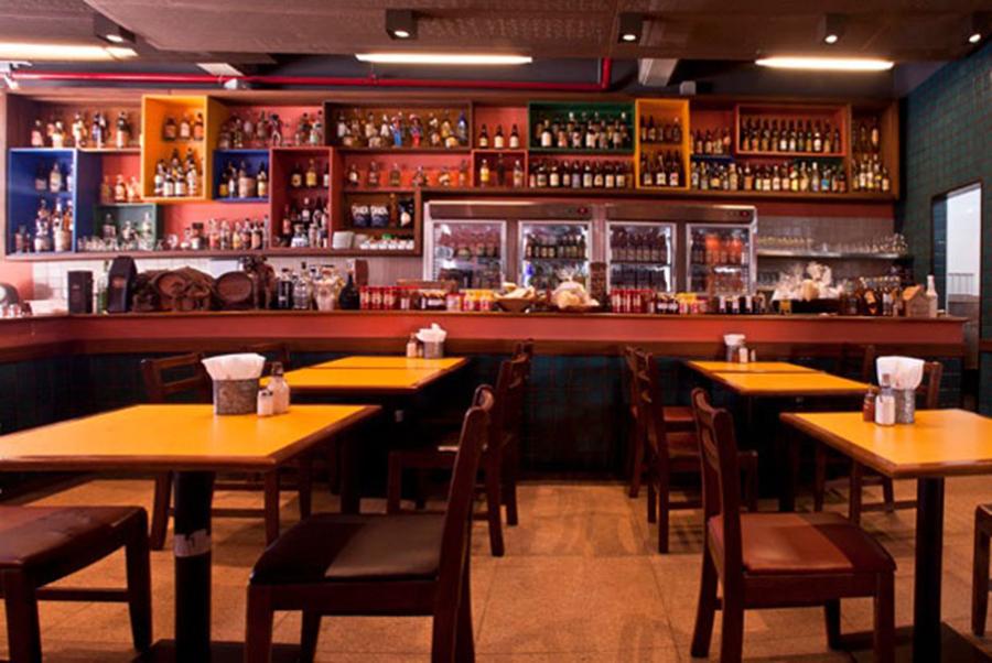 espaço com mesas e balcão com grande número de bebidas ao fundo no mocotó